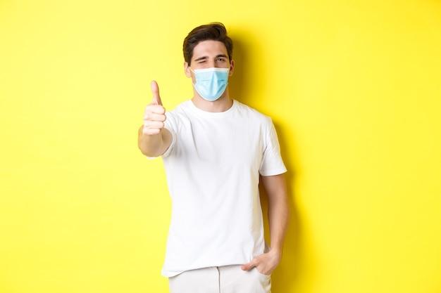 コロナウイルスの概念、パンデミックおよび社会的距離。親指を立ててウインク、黄色の背景を示す医療マスクの自信を持って若い男