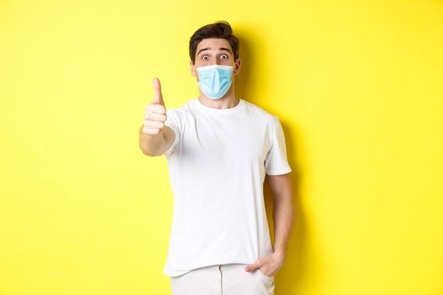 코로나 바이러스, 전염병 및 사회적 거리두기의 개념. 뭔가 멋진 노란색 배경처럼 승인에 엄지 손가락을 보여주는 의료 마스크에 인상적인 남자.
