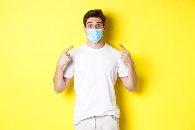 コロナウイルスの概念、パンデミックおよび社会的距離。顔、黄色の背景に医療マスクを指して驚いた若い男