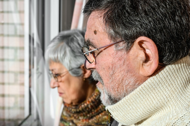 Концепция коронавирусного карантина и социального дистанцирования. пожилые супружеские пары, дома глядя через окно с обеспокоенным выражением. остаться дома. пожилой и пенсионерский образ жизни.
