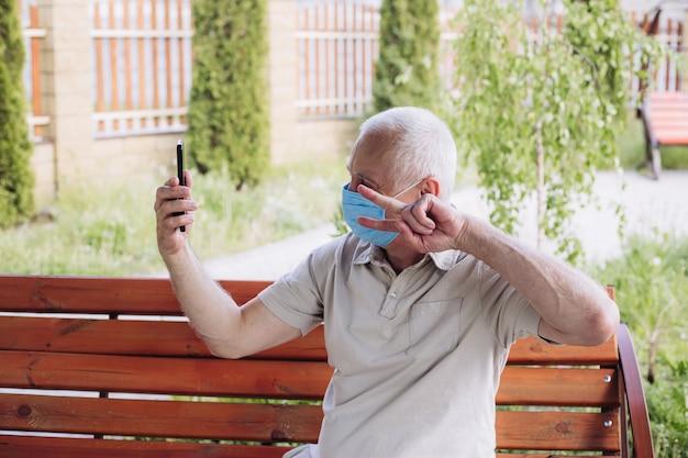コロナウイルス検疫、コロナウイルス、電話を使用してselfieを作る医療用フェイスマスクを持つ男の概念。