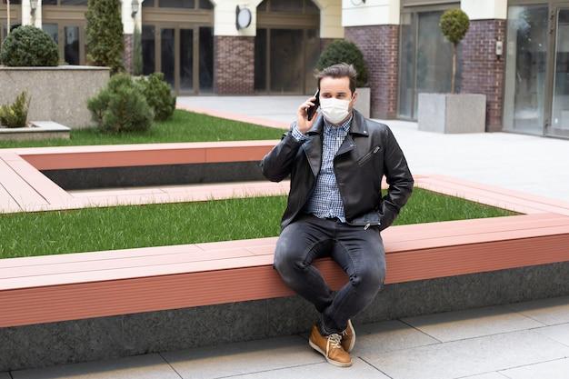 コロナウイルスの検疫、電話を使用してニュースを検索する医療用フェイスマスクを持つ男の概念。大気汚染