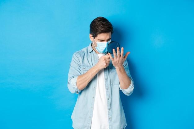 코로나바이러스, 사회적 거리 및 전염병의 개념. 파란색 배경 위에 서서 돋보기를 통해 손바닥을 바라보는 의료 마스크를 쓴 남자