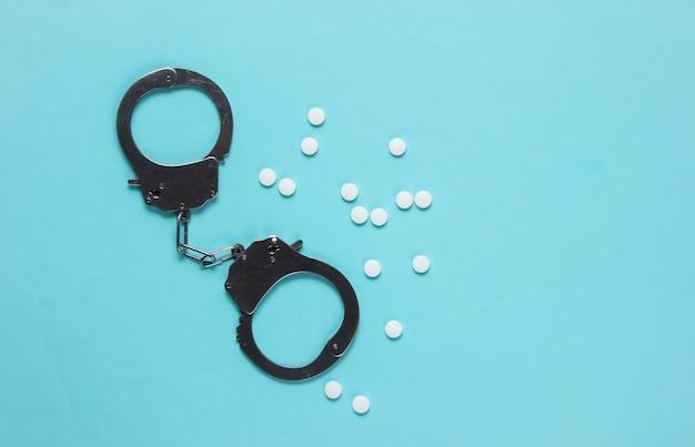 Понятие коррупции в медицине. таблетки и наручники на синем фоне. медицинский натюрморт. наказание за преступление.