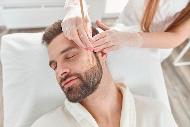 미용 및 얼굴의 개념. 한 여성 미용사가 제모를 왁싱하는 남자의 얼굴과 수염 모델링을합니다. 왁스로 탈모.