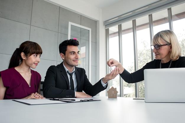 Концепция ковенанта покупки или аренды дома. супруги супруги получают ключ от дома после удачной покупки дома. подрядчики доставляют ключи покупателям дома.