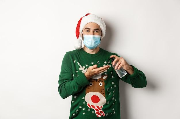 Covid-19 및 크리스마스 휴일의 개념입니다. 얼굴 마스크와 스웨터를 입은 백인 남자는 살균제로 깨끗한 손을 사용하고 흰색 배경 위에 서 있습니다.