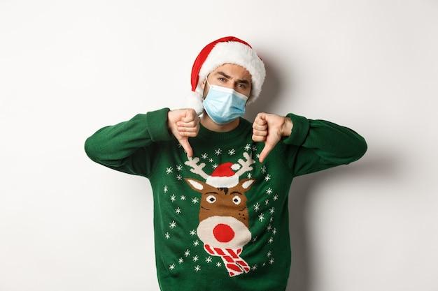 Covid-19とクリスマス休暇の概念。白い背景の上に立って、親指を下に見せてフェイスマスクとサンタ帽子の不機嫌な男