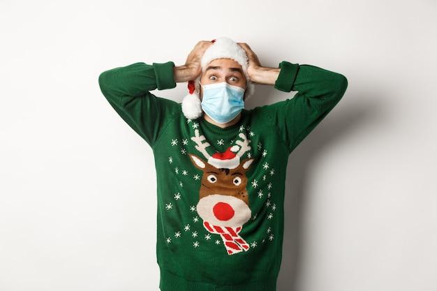 Covid-19 및 크리스마스 휴일의 개념입니다. 의료용 마스크와 산타 모자를 쓴 흥분되고 매우 행복한 남자가 놀란 흰색 배경을 보고 있다