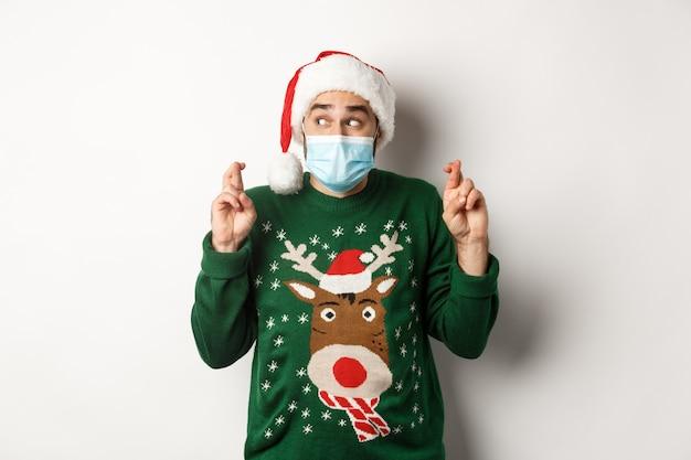 Covid-19 및 크리스마스 휴일의 개념입니다. 얼굴 마스크와 산타 모자를 쓴 흥분한 남자가 손가락을 꼬고 소원을 빌고 흰색 배경 위에 서 있다
