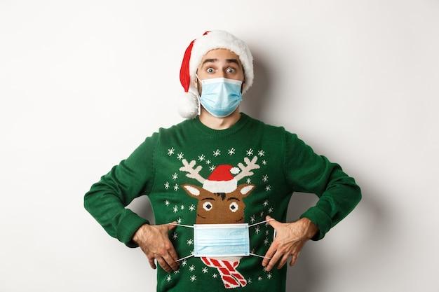 Covid-19 및 크리스마스 휴일의 개념입니다. 웃긴 남자는 흰색 배경 위에 서 있는 그의 스웨터 사슴에 얼굴 마스크를 쓰고