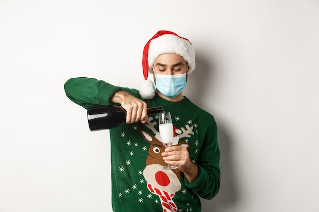 Covid-19 및 크리스마스 휴일의 개념입니다. 얼굴 마스크와 산타 모자를 쓴 행복한 남자, 새해 파티를 축하하고 샴페인 한 잔, 흰색 배경