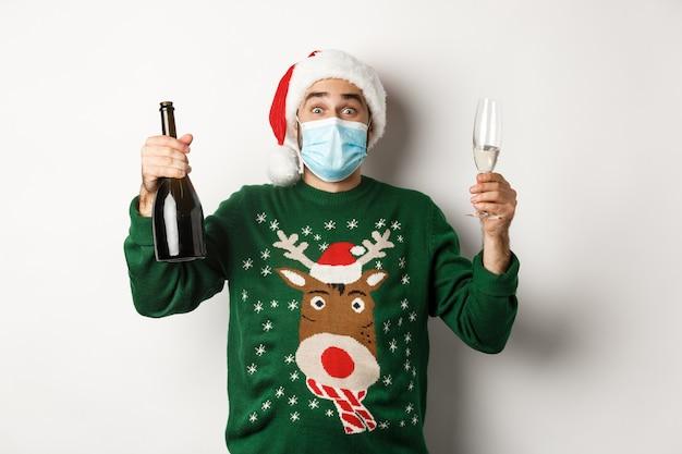 Covid-19 및 크리스마스 휴일의 개념입니다. 얼굴 마스크를 쓴 행복한 남자와 샴페인으로 새해를 축하하는 산타 모자, 흰색 배경 위에 서 있는