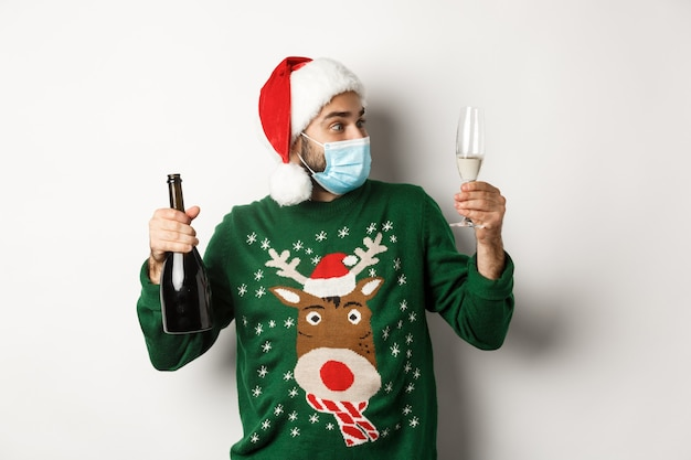 Covid-19 및 크리스마스 휴일의 개념입니다. 의료 마스크와 산타 모자를 쓴 남자가 샴페인 한 잔을 즐기고 새해를 축하하며 흰색 배경 위에 서 있습니다.
