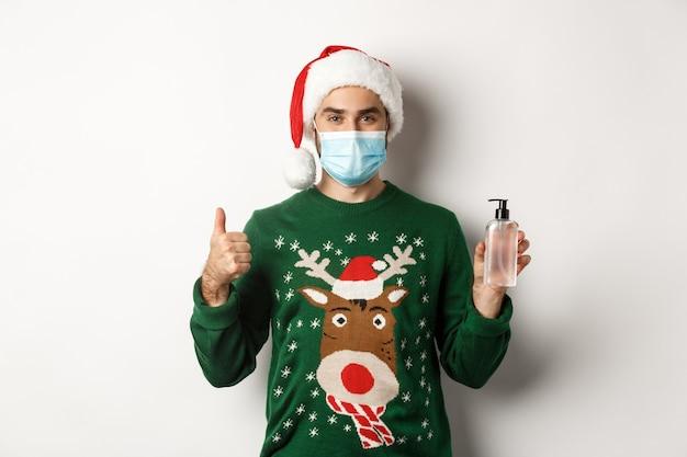 Covid-19 및 크리스마스 휴일의 개념입니다. 손 소독제를 추천하는 남자, 엄지손가락과 소독제를 보여주고, 산타 모자, 흰색 배경이 있는 의료용 마스크를 쓰고 있습니다.