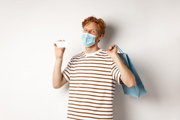 Понятие о covid-19 и образе жизни. счастливый молодой покупатель в лицевой маске, держащей хозяйственную сумку и показывающей пластиковую кредитную карту, покупая со скидками, на белом фоне.