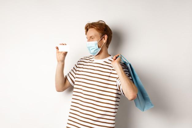 Covid-19와 쇼핑의 개념입니다. 얼굴 마스크를 쓴 행복한 젊은 쇼핑객은 종이 가방을 들고 플라스틱 신용 카드를 보여주고 할인으로 구매하고 흰색 배경을 가지고 있습니다.