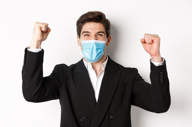 Covid-19, 비즈니스 및 사회적 거리의 개념. 양복과 의료용 마스크를 쓴 잘생긴 남자의 클로즈업, 기뻐하고 이기고, 손을 들고, 예를 외칩니다.