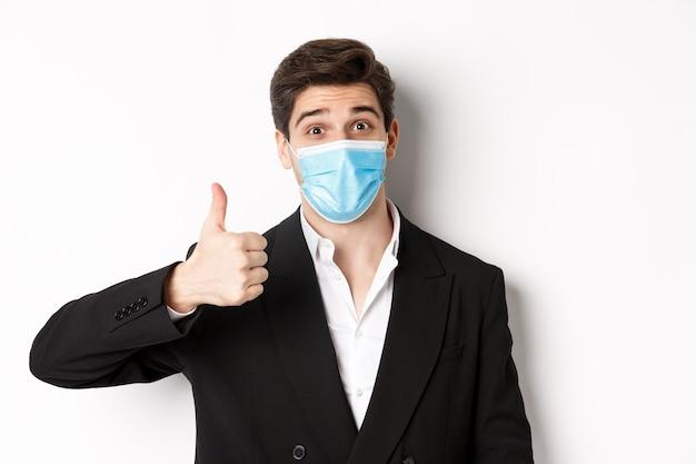 Covid-19, 비즈니스 및 사회적 거리의 개념. 검은 양복과 의료용 마스크를 쓴 행복한 사업가의 클로즈업, 엄지손가락을 위로 올려 칭찬, 흰색 배경