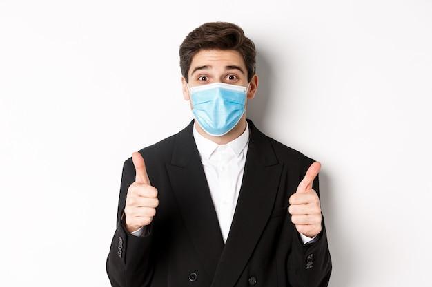 Covid-19の概念、ビジネスおよび社会的距離。黒のスーツと医療マスクで幸せなビジネスマンのクローズアップ、親指を立てて、褒め言葉、白い背景を作る