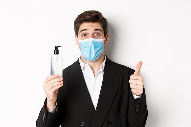 Covid-19の概念、ビジネスおよび社会的距離。白い背景に立って、親指と手の消毒剤を示す、スーツと医療マスクで満足しているハンサムな男のクローズアップ。