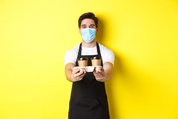 Covid-19、カフェ、社会的距離の概念。黄色の背景に黒いエプロンで立って、持ち帰り用のカップでコーヒーを提供する医療マスクのバリスタ。
