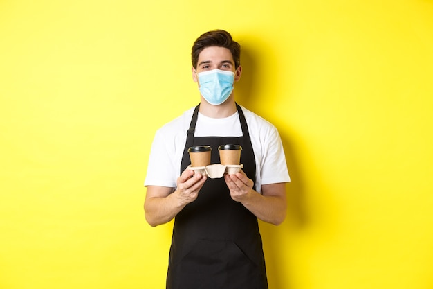 Covid-19, 카페 및 사회적 거리의 개념. 노란색 배경에 검은 앞치마에 서서 테이크아웃 컵에 커피를 제공하는 의료 마스크를 쓴 바리스타