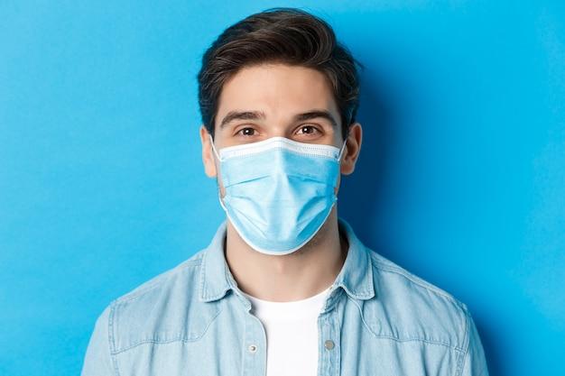 Covid-19、パンデミックおよび検疫の概念。青い背景の上に立って、カメラを見ている医療マスクの幸せな男のクローズアップ。