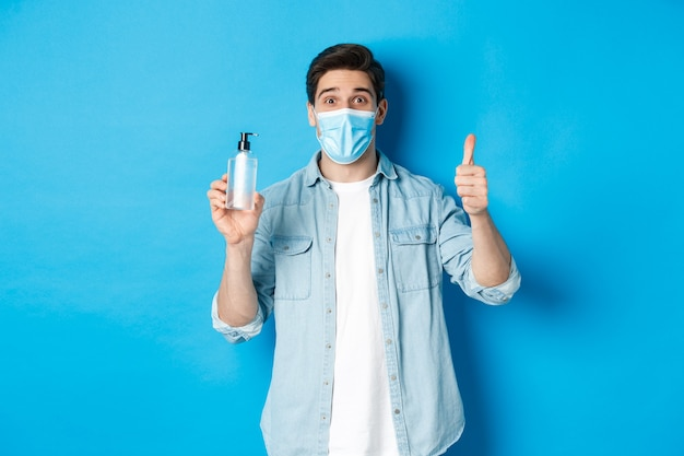Covid-19の概念、パンデミックおよび社会的距離。医療マスクの陽気な男、手指消毒剤と親指を立てて、消毒剤をお勧めし、青い背景に立って