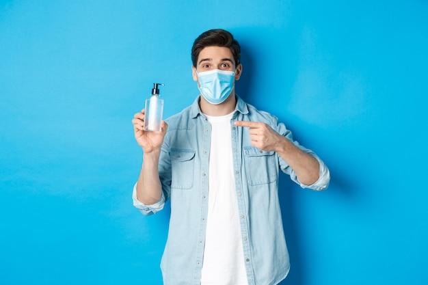 Covid-19の概念、パンデミックおよび社会的距離。医療マスクのハンサムな男は、青い背景の上に立って、消毒剤を指して、手の消毒剤を使用するようにアドバイスします