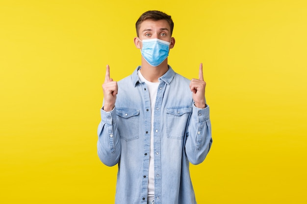 Covid-19 전염병 발병의 개념, 코로나바이러스 사회적 거리 동안의 생활 방식. 의료용 마스크를 쓴 잘생긴 백인 남자가 위를 올려다보며 위쪽 배너, 노란색 배경을 가리키고 있습니다.