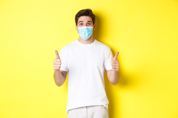 Covid-19の概念、検疫およびライフスタイル。何か良い黄色の背景のように、親指を立てる、承認する、または「はい」と言う医療マスクの幸せな男。