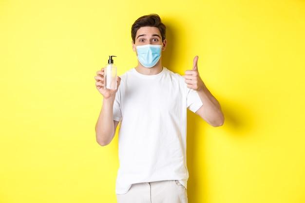 Covid-19の概念、検疫およびライフスタイル。優れた手の消毒剤を示し、親指を立て、消毒剤、黄色の背景を推奨する医療マスクの満足している若い男。