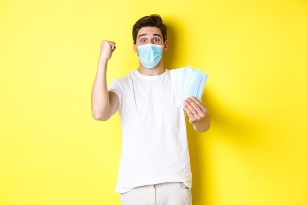 Covid-19の概念、検疫および予防措置。幸せな男が勝利し、何かを祝うために手を上げ、医療マスクを与え、黄色の背景に立っています。
