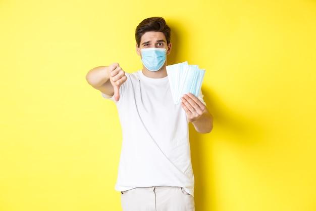 Covid-19, 격리 및 예방 조치의 개념. 실망하고 엄지를 아래로 보여주는 남자는 노란색 배경 위에 서있는 나쁜 의료 마스크를 권장하지 않습니다.