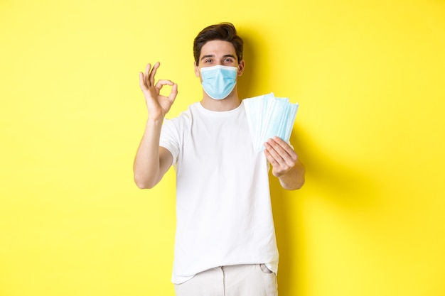 Covid-19の概念、検疫および予防措置。黄色の背景の上に立って、大丈夫な兆候を示し、医療マスクを与える満足のいく男