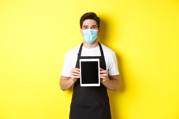 Covid-19, 중소기업 및 전염병의 개념. 노란색 배경 위에 서 태블릿 화면을 보여주는 의료 마스크에 바리 스타 웃 고.