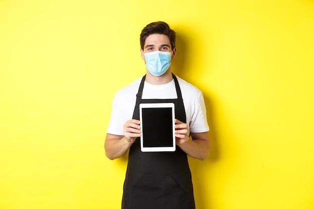 Covid-19、中小企業およびパンデミックの概念。黄色の背景の上に立って、タブレット画面を表示する医療マスクでバリスタを笑顔。