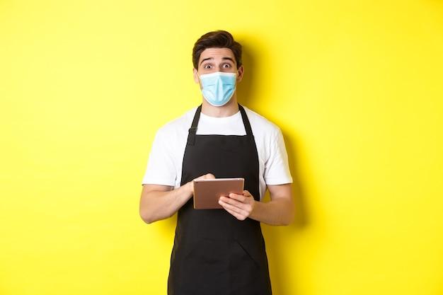 Covid-19, 중소기업 및 전염병의 개념. 노란색 배경 위에 서 디지털 태블릿을 들고 검은 앞치마와 의료 마스크 복용 순서에 웨이터.