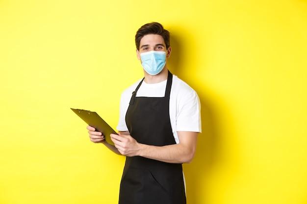 Covid-19、中小企業および検疫の概念。医療マスクと黒いエプロンで注文を受け、クリップボードを保持し、黄色の背景の上に立っている若い男性の売り手。