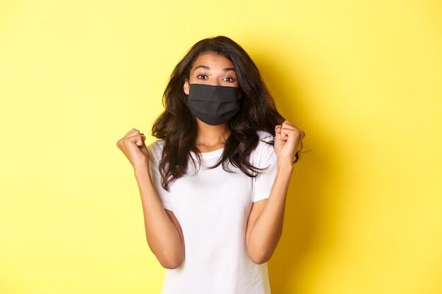 Covid-19, 사회적 거리 및 생활 방식의 개념. 쾌활한 아프리카계 미국인 여성은 검은색 얼굴 마스크를 쓰고 주먹을 쥔 채 기뻐하고 웃고, 상을 받고 노란색 배경을 가지고 있습니다.