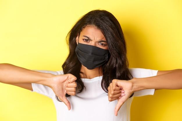 Covid-19の概念、社会的距離とライフスタイル。フェイスマスクで怒っているアフリカ系アメリカ人の女の子のクローズアップ、不承認を表明し、何か悪い、黄色の背景に親指を下に表示します