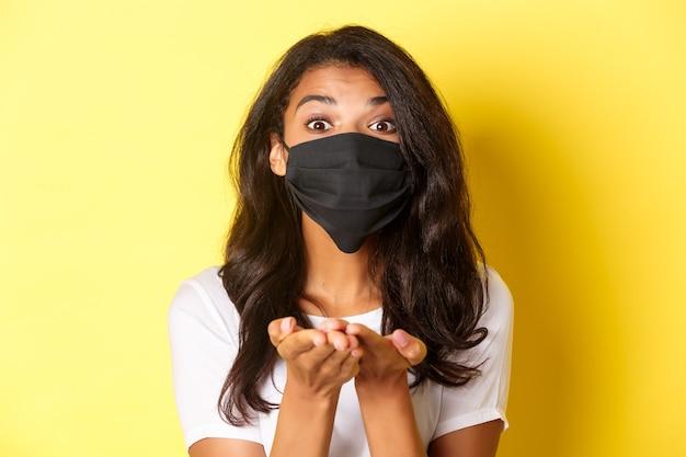 Концепция covid-19, социальное дистанцирование и образ жизни. крупный план прекрасной афро-американской девушки в черной маске для лица, дающей что-то, держащейся в руках, стоящей на желтом фоне