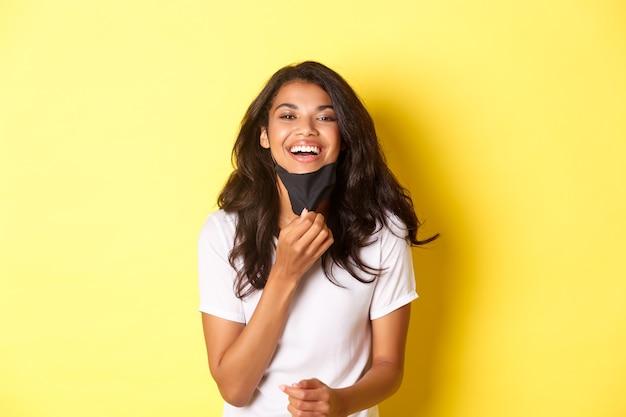 Covid-19, 사회적 거리 및 생활 방식의 개념. 아름다운 아프리카계 미국인 소녀의 이미지, 얼굴 마스크를 벗은 후 자유롭게 숨쉬는 것이 행복하고 기뻐하며 웃고 있는 노란색 배경