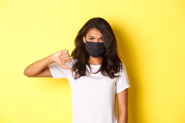 Covid-19, 사회적 거리 및 생활 방식의 개념. 검은 얼굴 마스크를 쓰고 싫어함을 표현하기 위해 엄지손가락을 아래로 보여주는 실망한 아프리카계 미국인 여성 모델의 이미지