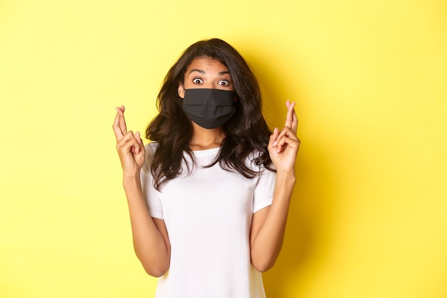 Covid-19, 사회적 거리 및 생활 방식의 개념. 흥분되고 희망적인 아프리카계 미국인 소녀, 소원을 빌고, 얼굴 마스크를 쓰고, 행운을 비는 손가락을 노란색 배경 위에 교차시키는 이미지.
