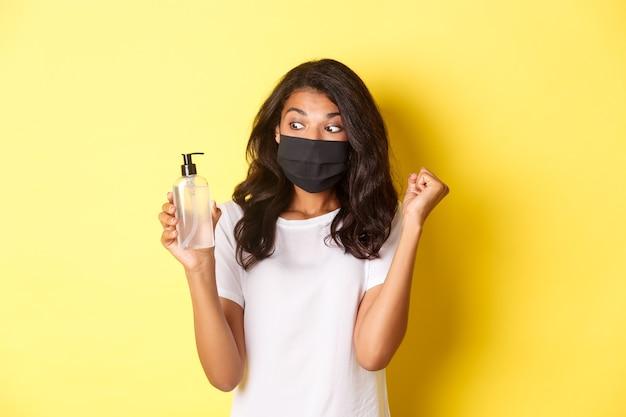 Covid-19の概念、社会的距離とライフスタイル。フェイスマスクと白いtシャツを着た幸せなアフリカ系アメリカ人女性の画像。優れた手指消毒剤を示し、黄色の背景に拳ポンプを作っています。