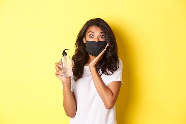 Концепция covid-19, социальное дистанцирование и образ жизни. изображение впечатленной афро-американской девушки в маске, показывающей хорошее дезинфицирующее средство для рук, рекомендующего продукт, желтый фон