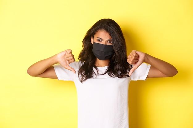 Covid-19, 사회적 거리 및 생활 방식의 개념. 화가 난 아프리카계 미국인 여성 시위자가 검은색 얼굴 마스크를 쓰고 엄지손가락을 아래로 내리고 실망한 표정을 짓고 있는 노란색 배경의 이미지.