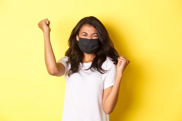 Covid-19の概念、社会的距離とライフスタイル。成功したアフリカ系アメリカ人の女の子、黒いフェイスマスクを着用し、何かを獲得し、手を上げ、喜びを叫び、勝利を祝います。